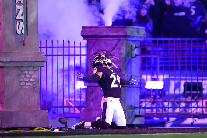 Baltimore Ravens safety Earl Thomas III kneels while taking the field prior to an NFL football game against the New England Patriots, Sunday, Nov. 3, 2019, in Baltimore. (AP Photo/Gail Burton)