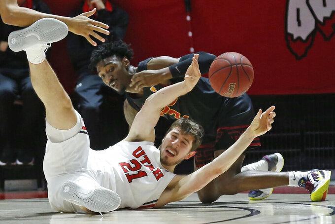 Utah forward Riley Battin (21) passes the ball as USC guard Jonah Mathews, rear, defends in the first half of an NCAA college basketball game Sunday, Feb. 23, 2020, in Salt Lake City. (AP Photo/Rick Bowmer)