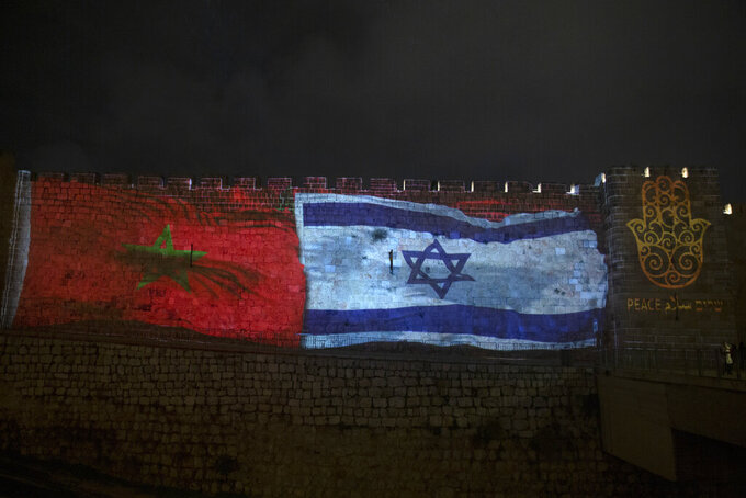 """FILE - In this Dec. 23, 2020 file photo, the national flags of Israel and Morocco are projected on the walls of the Old City of Jerusalem, along with the word """"peace,"""" in English, Hebrew, and Arabic. Two Israeli airlines launched their first commercial flights between Israel and Morocco on Sunday, July 25, 2021, less than a year after the countries officially normalized relations. (AP Photo/Maya Alleruzzo, File)"""