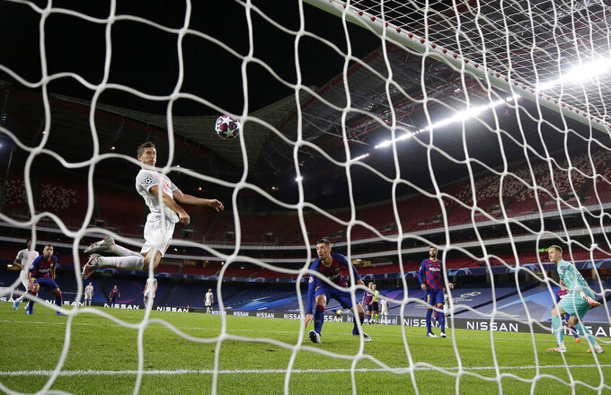 Bayern's Robert Lewandowski, left, leaps for a header to score past Barcelona's goalkeeper Marc-Andre ter Stegen, right, during the Champions League quarterfinal match between FC Barcelona and Bayern Munich at the Luz stadium in Lisbon, Portugal, Friday, Aug. 14, 2020. (AP Photo/Manu Fernandez/Pool)
