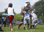 Michael Whitlow becomes a human tackling dummy for children in the Inspiring Children to Excellence football program in Columbus, Ohio. Michael and his wife Maree were founders of the Columbus Inspiring Children to Excellence football program. (Doral Chenoweth III/The Columbus Dispatch via AP)