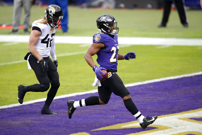 Baltimore Ravens running back J.K. Dobbins (27) scores a touchdown on a run as Jacksonville Jaguars safety Andrew Wingard (42) looks on during the first half of an NFL football game, Sunday, Dec. 20, 2020, in Baltimore. (AP Photo/Nick Wass)