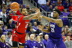 TCU center Kevin Samuel (21) passes the ball away from the defensive pressure by Texas Tech guard Kyler Edwards (0) during the first half of an NCAA college basketball game in Fort Worth, Texas, Tuesday, Jan. 21, 2020. (AP Photo/Ray Carlin)