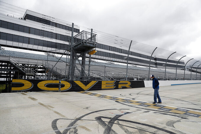 Mike Tatoian, president and CEO of Dover International Speedway, walks near the finish line while waiting for a news conference at the track, Monday, April 27, 2020, in Dover, Del. The track was scheduled to host a NASCAR auto race this weekend, but due to the COVID-19 outbreak, the race is bring run virtually on NASCAR's iRacing circuit. (AP Photo/Matt Slocum)