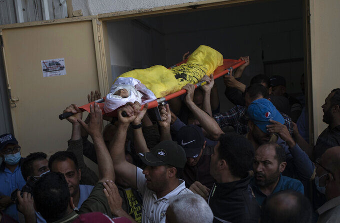 Palestinian mourners carry the body of 11-year-old Hussain Hamad, who was killed by an explosion during the ongoing conflict between Israel and Hamas, out of the morgue during his funeral in Beit Hanoun, northern Gaza Strip, Tuesday, May 11, 2021. (AP Photo/Khalil Hamra)