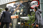 "People walk past a theater where the film ""Demon Slayer: Kimetsu no Yaiba the Movie: Mugen Train"" is screened on its opening day, Oct. 16, 2020. ""Demon Slayer,"" directed by Haruo Sotozaki, has become the biggest grossing film for Japan, including live-action films, and has struck a chord with pandemic-era Japan, and possibly with the world. (Tsuyoshi Ueda/Kyodo News via AP)"