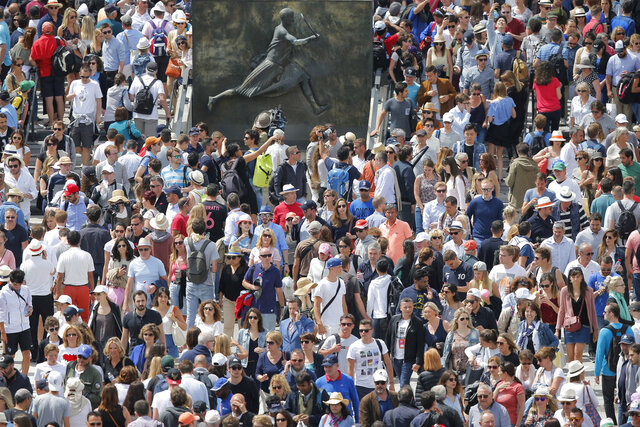 FILE - In this June 4, 2017 file photo, spectators crowd around a bronze plaque of French tennis player Suzanne Lenglen at the French Open tennis tournament at the Roland Garros stadium, in Paris. The French Tennis Federation says up to 60% of the stands can be filled with fans when play starts in September at Roland Garros. The clay-court tournament had been scheduled to start on May 24 but was postponed to Sept. 20 because of the coronavirus pandemic. (AP Photo/Michel Euler, File)