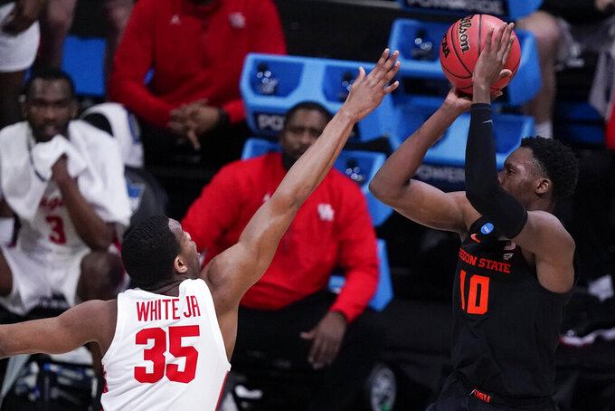 Oregon State forward Warith Alatishe (10) shoots on Houston forward Fabian White Jr. (35) during the first half of an Elite 8 game in the NCAA men's college basketball tournament at Lucas Oil Stadium, Monday, March 29, 2021, in Indianapolis. (AP Photo/Michael Conroy)