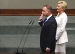Poland's conservative President Andrzej Duda,left, being sworn in for his second five-year term by lawmakers at the parliament in Warsaw, Poland, Thursday, Aug. 6, 2020. As precaution against the coronavirus spread all lawmakers were wearing masks. First Lady Agata Kornhauser-Duda is standing by Duda.(AP Photo/Czarek Sokolowski)