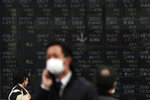 People walk past an electronic stock board showing Japan's Nikkei 225 index at a securities firm in Tokyo Tuesday, Feb. 25, 2020. Shares are mostly lower in Asia on Tuesday after Wall Street suffered its worst session in two years, with the Dow Jones Industrial Average slumping more than 1,000 points on fears that a viral outbreak that began in China will weaken the world economy.(AP Photo/Eugene Hoshiko)