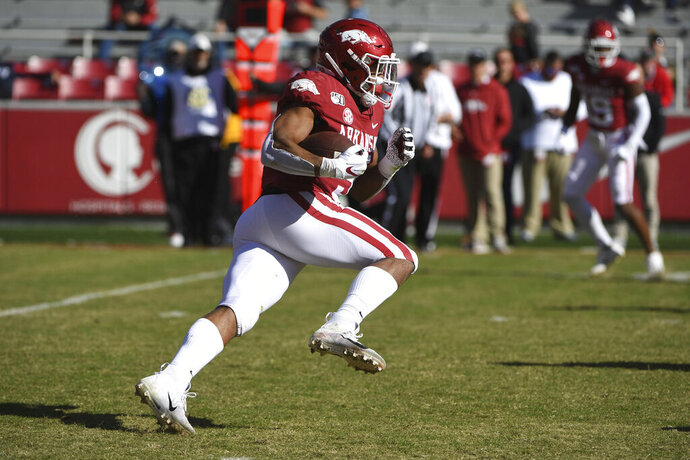 Arkansas running back Rakeem Boyd finds a hole in the Western Kentucky defense as he runs for an 86-yard touchdown during the second half of an NCAA college football game, Saturday, Nov. 9, 2019, in Fayetteville, Ark. (AP Photo/Michael Woods)