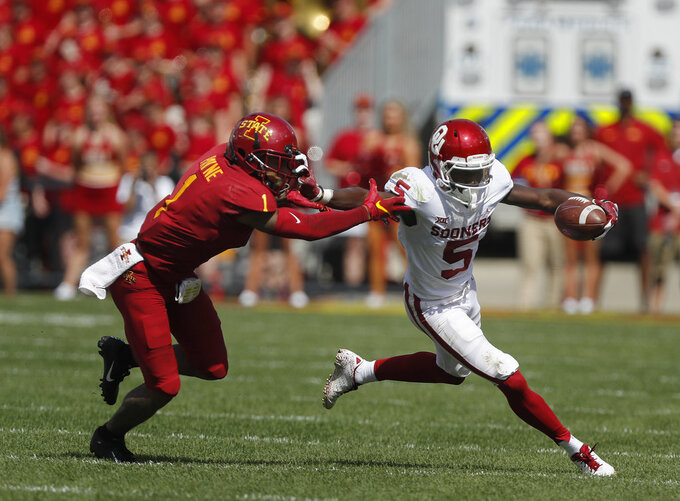 Oklahoma wide receiver Marquise Brown, right, runs the ball as he fends off Iowa State defensive back D'Andre Payne, left, during the first half of an NCAA college football game, Saturday, Sept. 15, 2018, in Ames. (AP Photo/Matthew Putney)