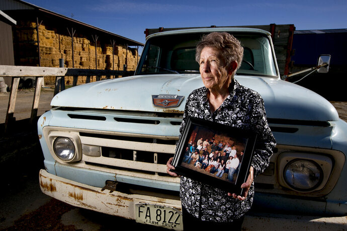 Gerry Jensen poses for a portrait with a photograph of her extended family at her family's farm on Wednesday, Sept. 25, 2019, in Benjamin, Utah. Her husband, Ronald Jensen, 87, currently heads up work on the farm, which was built by his grandfather in the 1860's according to Gerry. Their son Eric currently lives on the property, another son, Ryan, lives next door, and Jensen stated that they and their siblings will eventually take over the family farm. (Isaac Hale/The Daily Herald via AP)
