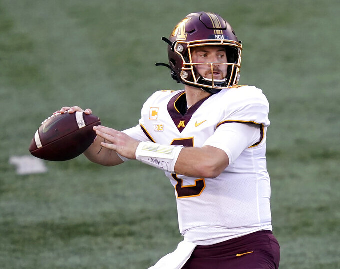 FILE - In this Nov. 7, 2020, file photo, Minnesota quarterback Tanner Morgan drops back to throw during the first half of an NCAA college football game against Illinois in Champaign, Ill. Morgan has big goals and an even bigger inspiration in mind for his fourth and perhaps final college season, following his father's death this summer after a bout with brain cancer. (AP Photo/Charles Rex Arbogast, File)