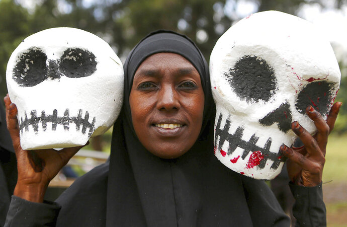 South Sudanese and Kenyan activists, some carrying mock skulls, as they protest against South Sudanese officials allegedly benefiting from the civil war and laundering money through Kenyan banks, in downtown Nairobi, Kenya Thursday, Oct. 11, 2018. Activists and refugees pressured Kenya's government to act against South Sudanese officials who have been sanctioned by the United Nations and are thought to be living freely in Kenya. (AP Photo/Brian Inganga)