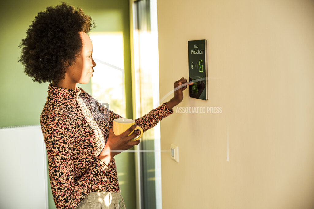 Young woman unlocking home automation device on wall