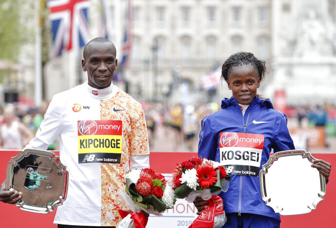 FILE - In this Sunday, April 28, 2019 file photo, women's race winner Kenya's Brigid Kosgei, right, and men's race winner Kenya's Eliud Kipchog pose after the 39th London Marathon in London. Olympic marathon champion Eliud Kipchoge was named on Kenya's team on Friday Jan. 31, 2020 to defend his title at this year's Tokyo Games, and Brigid Kosgei will lead Kenya's gold medal hopes in the women's race after she ran 2:14.04  in Chicago last year to break the world record for a woman running in a mixed race. (AP Photo/Alastair Grant, File)