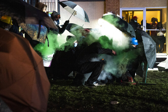A demonstrator is shot with a less-than-lethal munition from police outside the Brooklyn Center Police Department while protesting the shooting death of Daunte Wright, Tuesday, April 13, 2021, in Brooklyn Center, Minn. (AP Photo/John Minchillo)