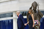 President Donald Trump holds first lady Melania Trump's hand as they visit Saint John Paul II National Shrine, Tuesday, June 2, 2020, in Washington. (AP Photo/Patrick Semansky)