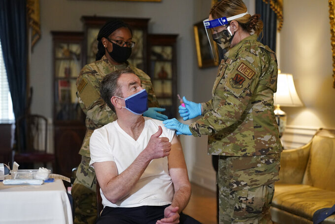 Virginia Gov. Ralph Northam gives a thumbs up after he receives a COVID-19 vaccination from Lt. Col. Kris Clark, of the Virginia Air National Guard at the Governor's Mansion in Richmond, Va., Monday, March 15, 2021. Northam got a shot of the Johnson & Johnson coronavirus vaccine on Monday, joining the growing number of Virginians who are being inoculated against the potentially deadly disease. (AP Photo/Steve Helber)