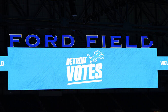 """Detroit Votes"" is displayed on the Ford Field scoreboard, Tuesday, Nov. 3, 2020, in Detroit. Michigan Secretary of State Jocelyn Benson cast her vote in a drop box at the Detroit Pistons' training facility and about 12 hours later, she witnessed ballots being rolled into Ford Field for a double-checking step of the election process. (AP Photo/Carlos Osorio)"