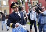 Damir Yusupov, 41, the captain of Ural Airlines A321, walks to attend a news conference in Ramenskoye, just outside Moscow, Russia, Thursday, Aug. 15, 2019.  The captain of a Russian passenger jet was hailed as a hero Thursday for landing his plane in a cornfield after it collided with a flock of gulls seconds after takeoff, causing both engines to malfunction. (AP Photo/Vladimir Shatilov)