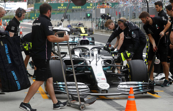 FILE - In this file photo dated Friday, Aug. 2, 2019, Pit crew work on the car of Mercedes driver Valtteri Bottas of Finland during the second practice session of the Hungarian Formula One Grand Prix at the Hungaroring racetrack in Mogyorod, northeast of Budapest, Hungary. The British-based Mercedes team announced Thursday Aug. 29, 2019, it has exercised the option to keep 30-year-old Finnish driver Bottas for the 2020 season, as teammate of world champion Lewis Hamilton. (AP Photo/Laszlo Balogh, FILE)