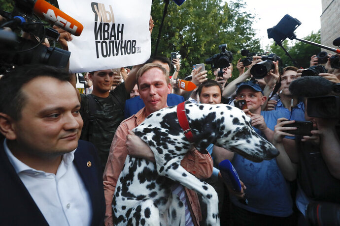 Prominent Russian investigative journalist Ivan Golunov, carry his dog as he leaves a Investigative Committee building in Moscow, Russia, Tuesday, June 11, 2019. In a surprising turnaround, Russia's police chief on Tuesday dropped all charges against a prominent investigative reporter whose detention sparked public outrage and promised to go after the police officers who tried to frame the journalist as a drug-dealer. (AP Photo/Alexander Zemlianichenko)