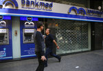 People pass by a closed bank, in Beirut, Lebanon, Wednesday, Oct. 30, 2019. Lebanese banks have been closed for the last two weeks as the government grapples with mass demonstrations that have paralyzed the country, but an even greater crisis may set in when they reopen Friday. (AP Photo/Hussein Malla)