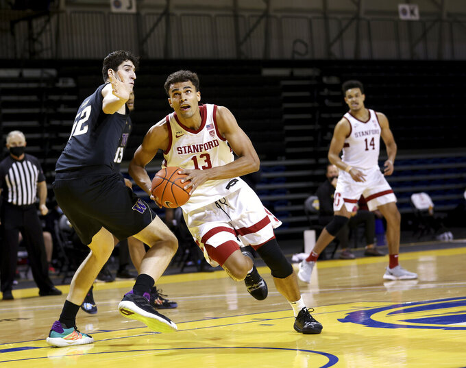 CORRECTS YEAR TO 2021 NOT 2020 - Stanford forward Oscar da Silva (13) drives the ball against Washington center Riley Sorn (52) during the first half of an NCAA college basketball game in Santa Cruz, Calif., Thursday, Jan. 7, 2021. (AP Photo/Josie Lepe)