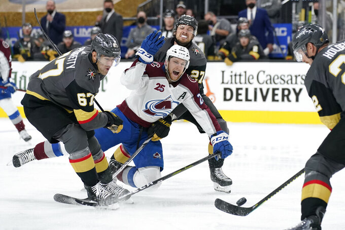 Vegas Golden Knights left wing Max Pacioretty (67) and Vegas Golden Knights defenseman Shea Theodore (27) knock Colorado Avalanche center Nathan MacKinnon (29) to the ice during the third period in Game 3 of an NHL hockey Stanley Cup second-round playoff series Friday, June 4, 2021, in Las Vegas. (AP Photo/John Locher)