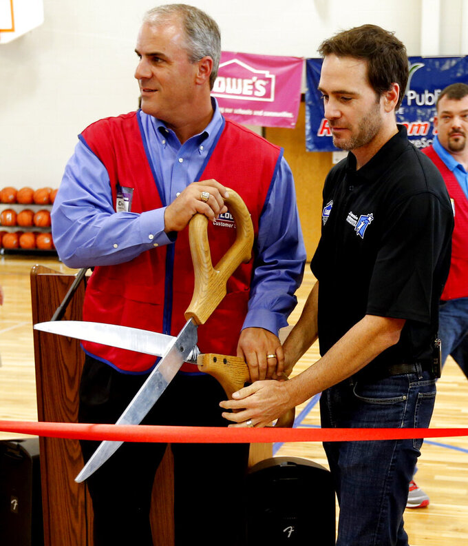 FILE  - This Thursday, Oct. 2, 2014, file photo shows Dennis Knowles, left, executive director of U.S. stores for Lowe's, NASCAR driver Jimmie Johnson participate in a ribbon-cutting ceremony at Highland East Junior High to celebrate the opening of three area school gyms, in Moore, Okla. Johnson and Lowe's were major contributors to rebuilding facilities after a 2013 tornado destroyed homes, business, and schools in Moore. NASCAR's nicest guy will run his final race this week and close a remarkable career. Jimmie Johnson's record-tying seven Cup titles are well celebrated, but his charitable work goes less noticed. The Jimmie Johnson Foundation has donated more than $12 million to schools and programs since it launched. (Steve Sisney/The Oklahoman via AP, File)