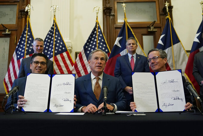 With the help of state Rep. Chris Paddie, left, and state Sen. Kelly Hancock, right, Texas Gov. Greg Abbott, center, speaks as two energy related bills he signed are displayed, Tuesday, June 8, 2021, in Austin, Texas. Abbot signed legislation into law to reform the Electric Reliability Council of Texas (ERCOT) and weatherize and improve the reliability of the state's power grid. (AP Photo/Eric Gay)