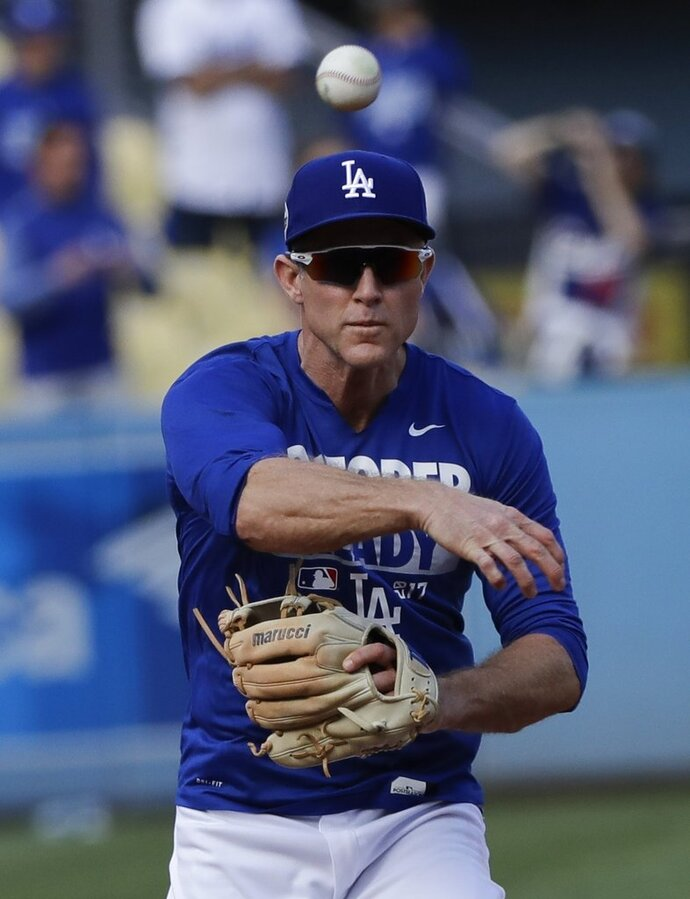 FILE - This Nov. 1, 2017 file photo shows Los Angeles Dodgers' Chase Utley warming up before Game 7 of baseball's World Series against the Houston Astros in Los Angeles. Utley appears headed back to the Los Angeles Dodgers. The free-agent infielder's gloves and cleats were in the Dodgers clubhouse on Tuesday, Feb. 13, 2018 and mail addressed to him was in a dressing stall. (AP Photo/David J. Phillip, file)