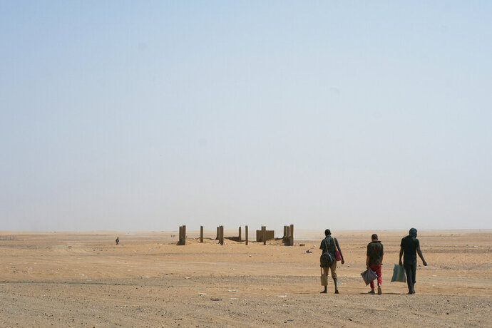 FILE - In this Sunday, June 3, 2018 file photo, three men head north towards Algeria after crossing the Assamaka border post in northern Niger. More than 80 African migrants were rescued on Thursday, Sept. 3, 2020 after being found in a remote stretch of the Sahara Desert where hundreds of others have died along the perilous journey in recent years, the International Organization for Migration said Tuesday, Sept. 8, 2020. (AP Photo/Jerome Delay, File)