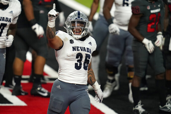 Nevada running back Toa Taua (35) celebrates after scoring a touchdown against UNLV during the second half of an NCAA college football game Saturday, Oct. 31, 2020, in Las Vegas. (AP Photo/John Locher)