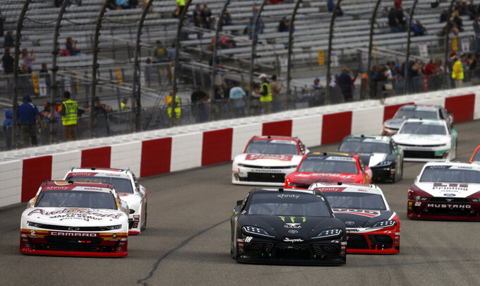 Riley Herbst (18) leads the field at the start of a NASCAR Xfinity Series auto race at Richmond International Raceway in Richmond, Va., Friday, April 12, 2019. (AP Photo/Steve Helber)