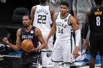 Brooklyn Nets forward Kevin Durant, left, clenches his fist next to Milwaukee Bucks forward Giannis Antetokounmpo (34) in the waning seconds of the Nets' 114-108 victory in Game 5 of a second-round NBA basketball playoff series Tuesday, June 15, 2021, in New York. (AP Photo/Kathy Willens)