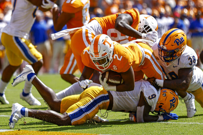 Tennessee running back Jabari Small (2) dives across the goal line for a touchdown as he's hit by Pittsburgh defensive back Brandon Hill (9) and linebacker Cam Bright (38) during the first half of an NCAA college football game Saturday, Sept. 11, 2021, in Knoxville, Tenn. (AP Photo/Wade Payne)