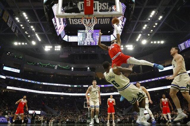Milwaukee Bucks' Eric Bledsoe fouls Sacramento Kings' Kent Bazemore as he shoots during the first half of an NBA basketball game Monday, Feb. 10, 2020, in Milwaukee. (AP Photo/Morry Gash)
