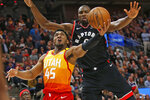 Toronto Raptors center Serge Ibaka, rear, defends against Utah Jazz guard Donovan Mitchell (45) who goes to the basket in the second half during an NBA basketball game Monday, March 9, 2020, in Salt Lake City. (AP Photo/Rick Bowmer)