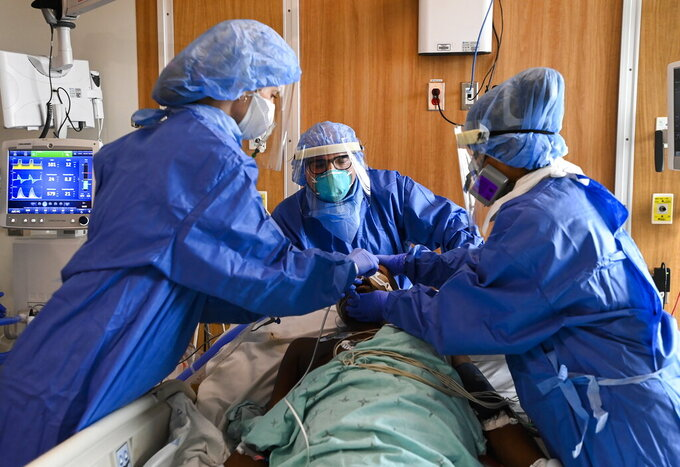 Health care staff provide life saving medical care to 60-year-old COVID-19 patient in the intensive care unit at the Humber River Hospital in Toronto on Tuesday, April 13, 2021. The patient was intubated and put on a ventilator successfully. (Nathan Denette/The Canadian Press via AP)