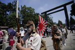 Visitors in Japanese Imperial army and navy uniforms stand at attention to pay their respects to the war dead at Yasukuni Shrine Saturday, Aug. 15, 2020, in Tokyo. Japan marked the 75th anniversary of the end of World War II. (AP Photo/Eugene Hoshiko)