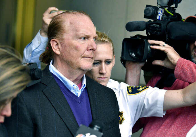FILE - In this May 24, 2019 file photo, chef Mario Batali departs after pleading not guilty, at municipal court in Boston, to an allegation that he forcibly kissed and groped a woman at a Boston restaurant in 2017. Batali waived his right to appear at a hearing on Friday, July 23 in Boston, and a hearing on defense motions was scheduled at a later date. (AP Photo/Josh Reynolds, File)