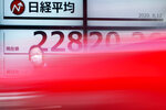 A man stands as a car drives by near an electronic stock board showing Japan's Nikkei 225 index at a securities firm in Tokyo Wednesday, Aug. 12, 2020. Shares were mostly lower in Asia on Wednesday after Wall Street pumped the brakes on its recent rally. (AP Photo/Eugene Hoshiko)
