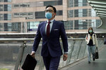 A man wearing protective face mask, walks on a street in the Central, the business district in Hong Kong, Wednesday, Feb. 12, 2020. China on Wednesday reported another drop in the number of new cases of a viral infection and 97 more deaths, pushing the total dead past 1,100 even as the country remains largely closed down to prevent the spread of the disease. (AP Photo/Kin Cheung)