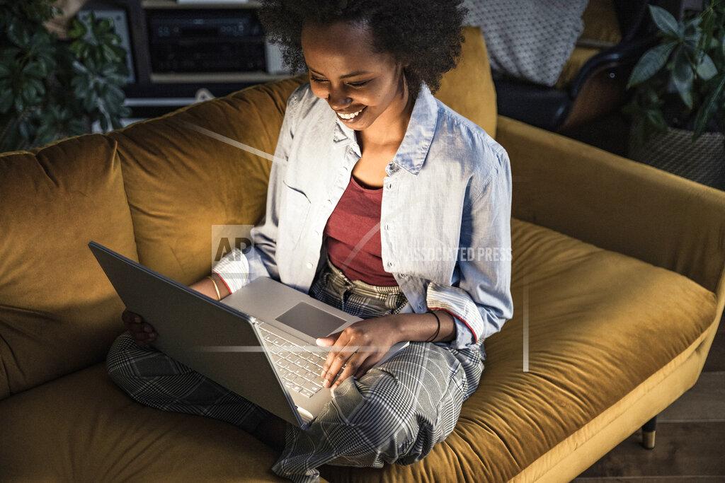 Smiling businesswoman using laptop while sitting on sofa