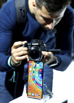 A man takes a picture of the new 'Huawei Mate 30' of China's smartphone manufacturer Huawei during an event in Munich, Germany, Thursday, Sept. 19, 2019. (AP Photo/Matthias Schrader)