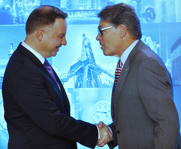 Poland's President Andrzej Duda, left, and U.S. Energy Secretary Rick Perry, right, shake hands during a ceremony in which Poland's main gas company PGNiG signed a long-term deal for liquefied gas deliveries with the U.S. firm Chenier, in Warsaw, Poland, Thursday, Nov. 8, 2018. (AP Photo/Czarek Sokolowski)