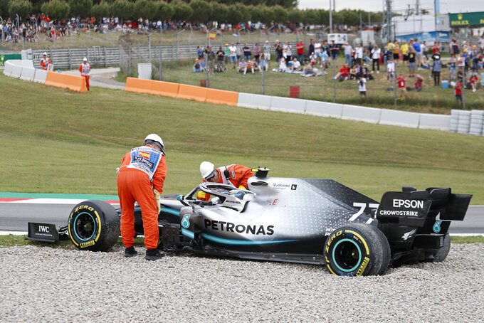 Track marshals check on Mercedes driver Valtteri Bottas of Finland after he skidded off the track into the gravel during free practice at the Barcelona Catalunya racetrack in Montmelo, just outside Barcelona, Spain, Saturday, May 11, 2019. The Spanish F1 Grand Prix race will be held on Sunday. (AP Photo/Joan Monfort)